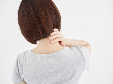 首をおさえる女性の写真